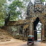 Photo of tuk tuk passing through Angkor Thom Gate in Siem Reap, Cambodia